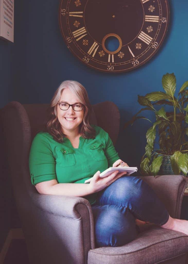 Jill Anderson sitting in chair in office